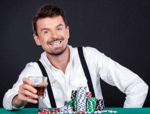 A high limit gambler with a lot of casino chips smiling with a drink in hand